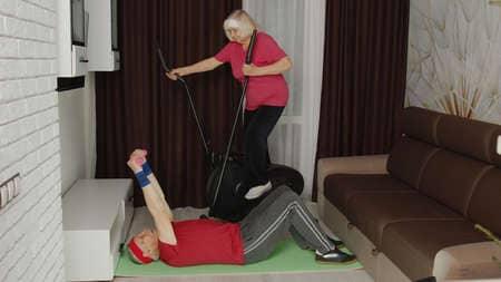 pratiquants sur un elliptique et un autre en abdos