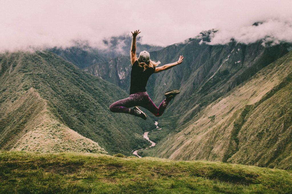 Femme qui saute en l'air devant un panorama de montagnes vertes