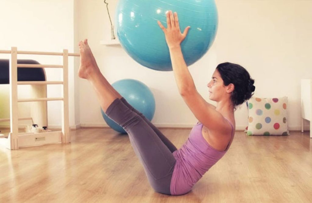 Pratiquante de Pilates tenant un gymball dans ses mains