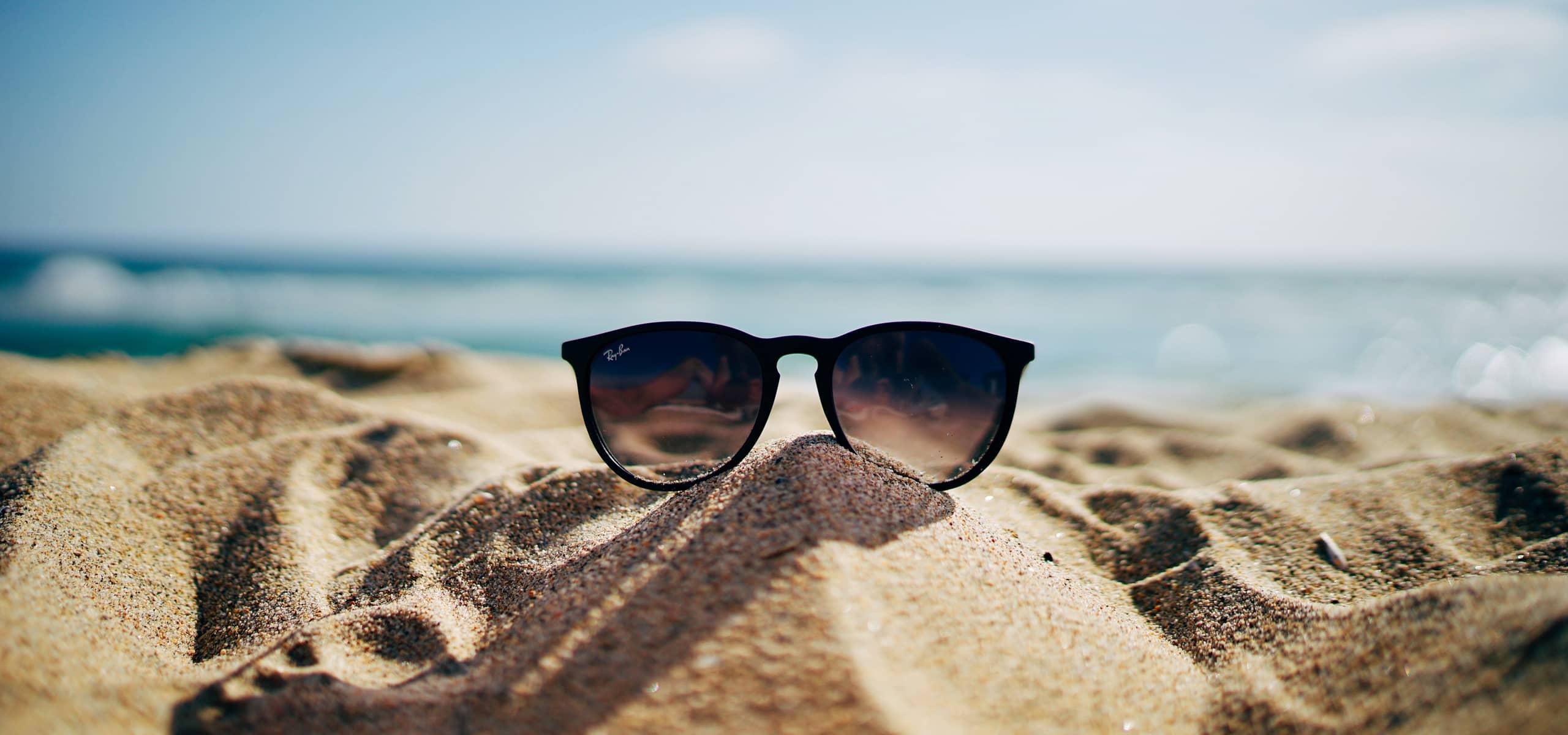 Des lunettes de soleil dans le sable